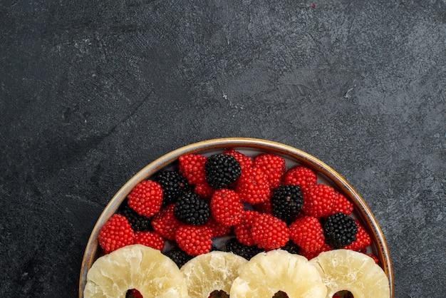 Top close view anneaux d'ananas séchés avec des baies de confiture sur le mur gris fruits secs raisin sec bonbon de sucre
