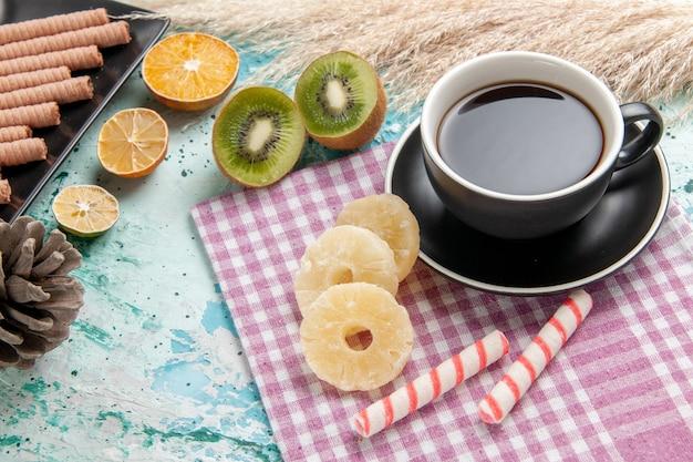 Top close view biscuits sucrés avec tasse de thé et anneaux d'ananas séchés sur la surface bleue