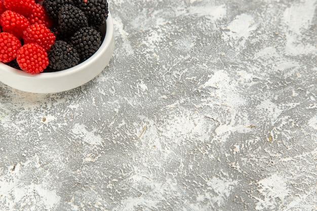 Top close view confitures de baies fraîches bonbons sucrés sur surface blanche