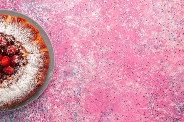Top close view délicieux gâteau aux fraises cuit avec du sucre en poudre sur le gâteau mural rose clair cuire au four biscuit au sucre biscuit tarte aux biscuits