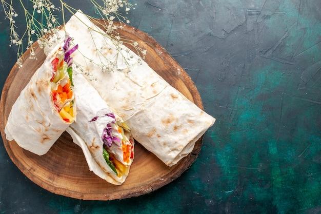 Top close view délicieux sandwich à la viande fait de viande grillée à la broche en tranches sur le bureau bleu