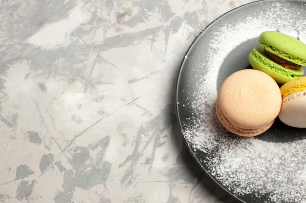 Top close view macarons français délicieux gâteaux colorés à l'intérieur de la plaque sur la surface blanche