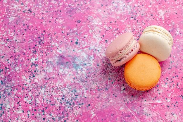 Top close view macarons français délicieux petits gâteaux sur le bureau rose cuire un gâteau sucré tarte au sucre confiture