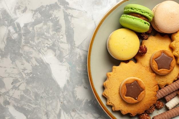 Top close view macarons français avec des gâteaux et des cookies sur une surface blanche