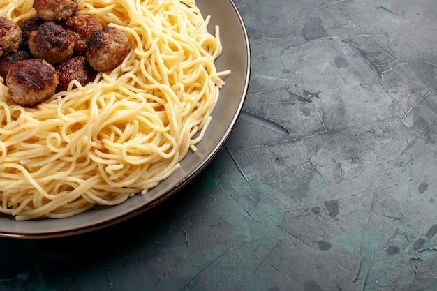 Top close view pâtes italiennes cuites avec des boulettes de viande sur la surface bleu foncé