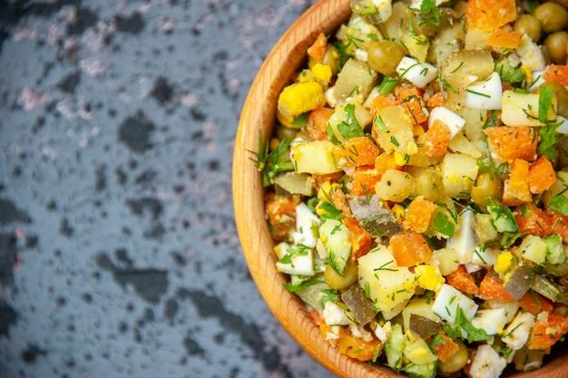 Top close view salade de légumes bouillis à l'intérieur de la plaque sur fond bleu