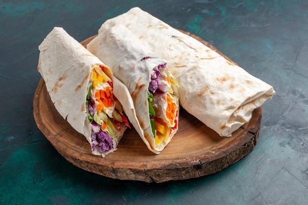 Top close view sandwich à la viande un sandwich fait de viande grillée à la broche en tranches sur une surface bleu foncé