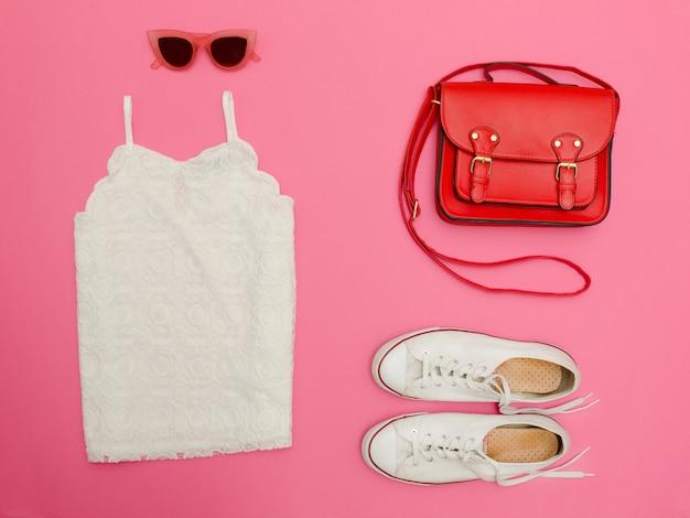 Top en dentelle blanche, sac à main rouge, baskets blanches et lunettes roses. fond rose vif, gros plan