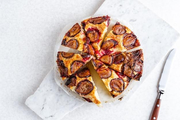 Top down vue de tarte aux prunes en tranches sur couleur claire
