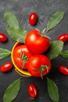 Top fermer voir un seau avec des tomates autour des tomates cerises et des feuilles de laurier sur fond sombre