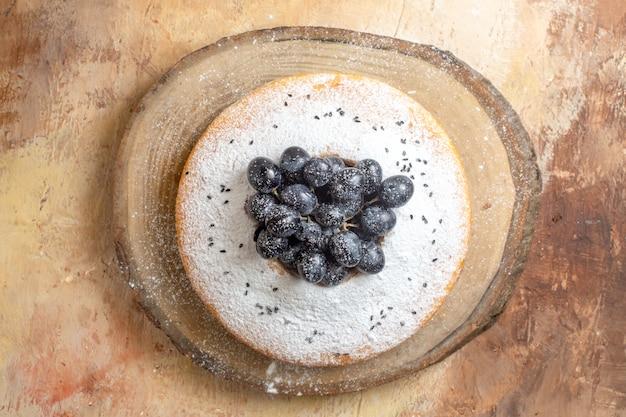 Top gâteau vue rapprochée un gâteau appétissant avec des raisins noirs sur la planche à découper