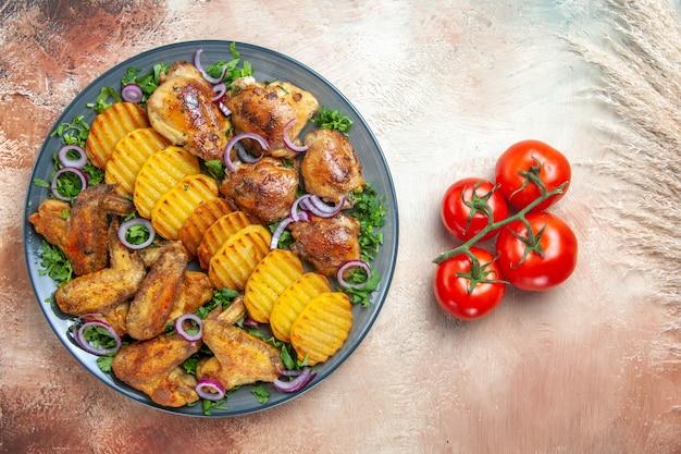 Top gros plan tomates poulet avec pédicelles ailes de poulet pommes de terre herbes oignons