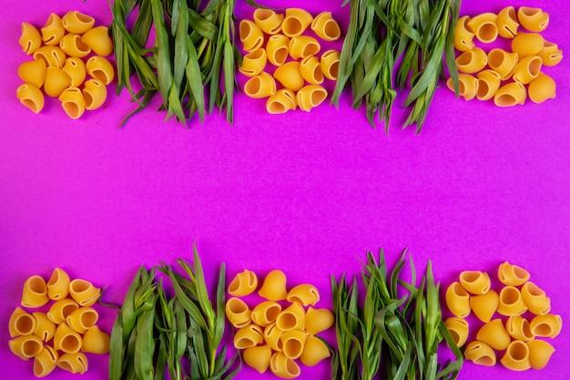 Top pâtes crues ditalini à l'estragon frais avec copie espace sur violet