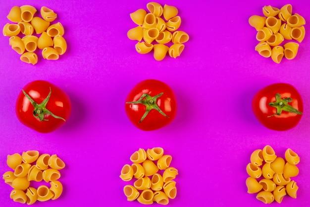 Top pâtes crues ditalini avec tomates fraîches sur violet
