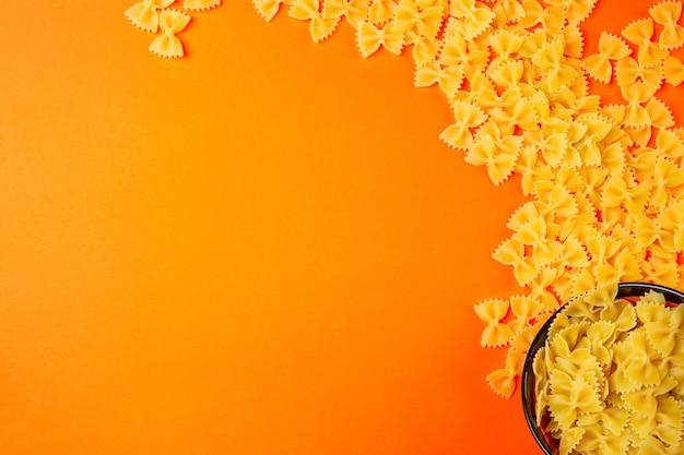 Top pâtes sèches farfalle avec copie espace sur orange