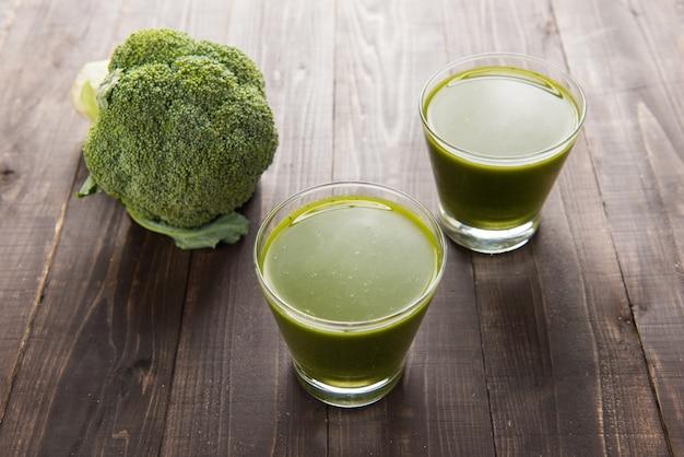 Top shot de jus de brocoli sur table en bois.