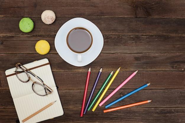 Top viev sur une tasse de café, des macarons, des crayons de couleur et un cahier