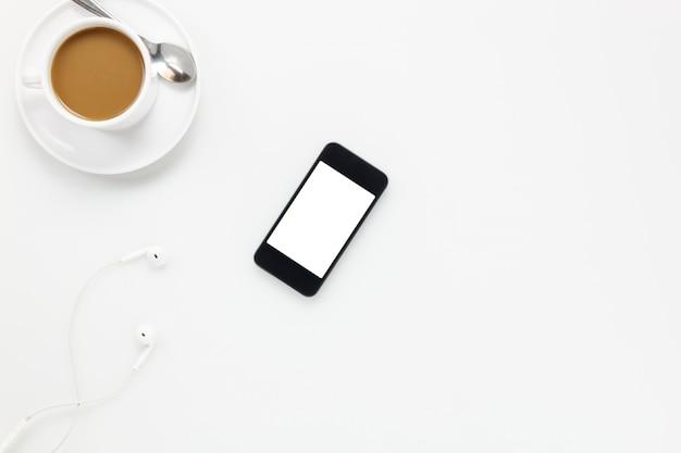 Top view accessoires bureau bureau.smartphones écouteurs et tasse de café sur fond blanc.