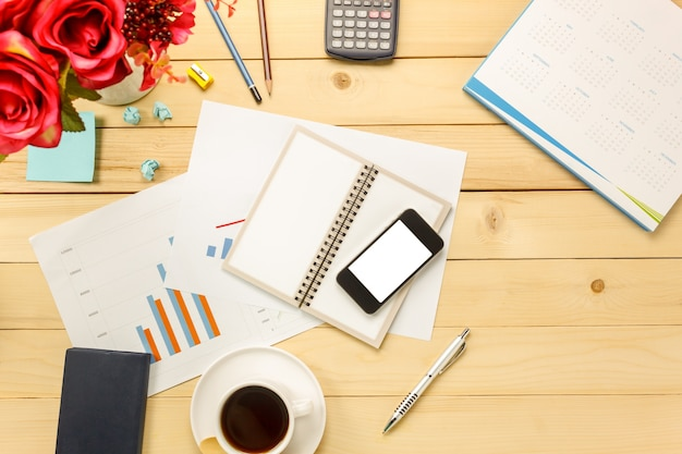 Top view business office les graphiques et les graphiques aussi cahier, café noir, fleur, stationnaire, stylo, calculatrice sur fond de bureau.