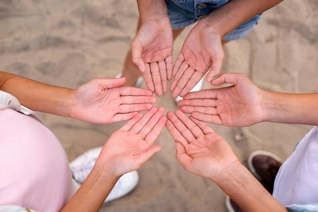 Top view kids faisant une fleur avec leurs mains