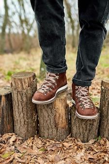Top viewoman debout avec des bottes de montagne de randonnée sur les feuilles d'automne et fond de bois