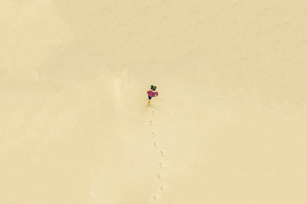 Top vue aérienne du jeune homme solitaire marcher dans le désert sur la texture de sable. concept perdu