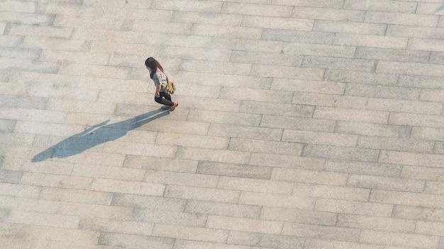 Top vue aérienne flou les gens marchent sur à travers le béton piétonnier.