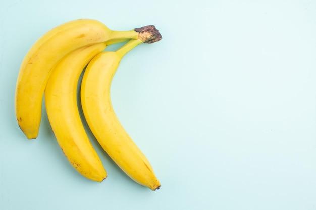 Top vue en gros plan bananes trois bananes rouges sur fond bleu