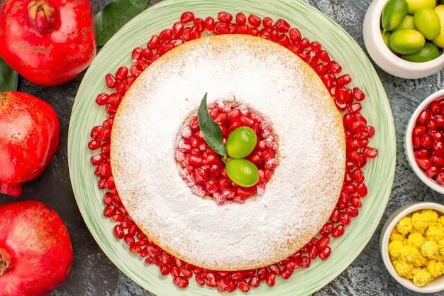 Top vue en gros plan du gâteau avec des bols de grenade à la grenade de baies et une assiette de gâteau
