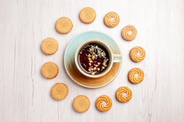 Top vue en gros plan du thé avec des biscuits tasse blanche de tisane et des biscuits appétissants autour sur le tableau blanc