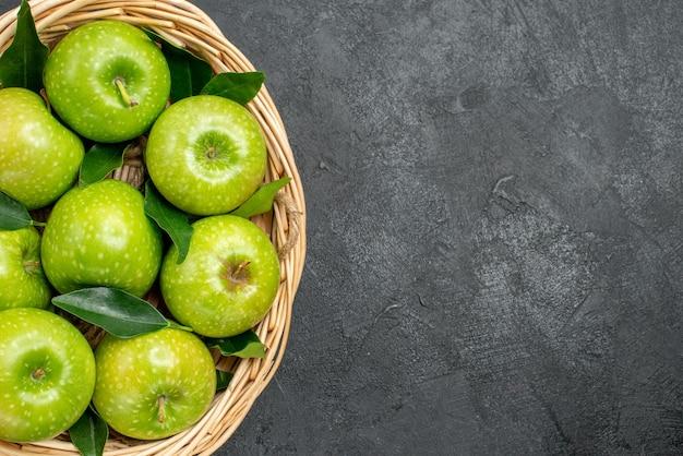Top vue en gros plan des pommes dans le panier panier en bois des pommes appétissantes avec des feuilles vertes