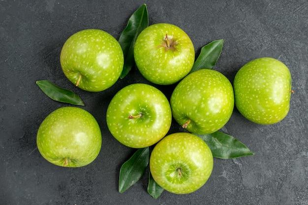Top vue en gros plan pommes sept pommes vertes avec des feuilles sur le tableau noir