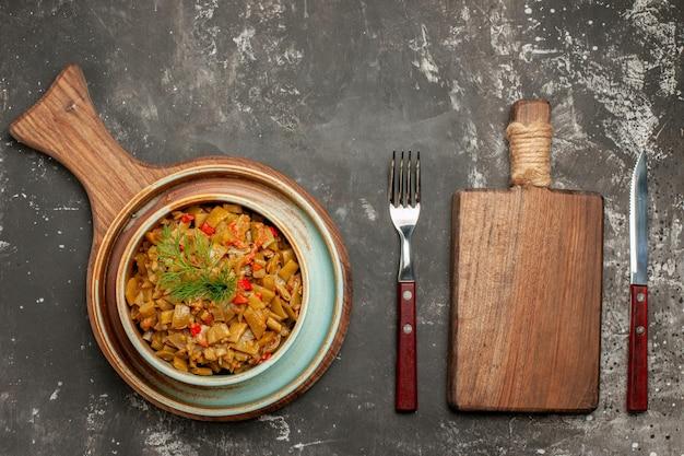 Top vue en gros plan tomates et haricots verts bol de haricots avec tomates à côté de la planche à découper couteau et fourchette sur la table noire