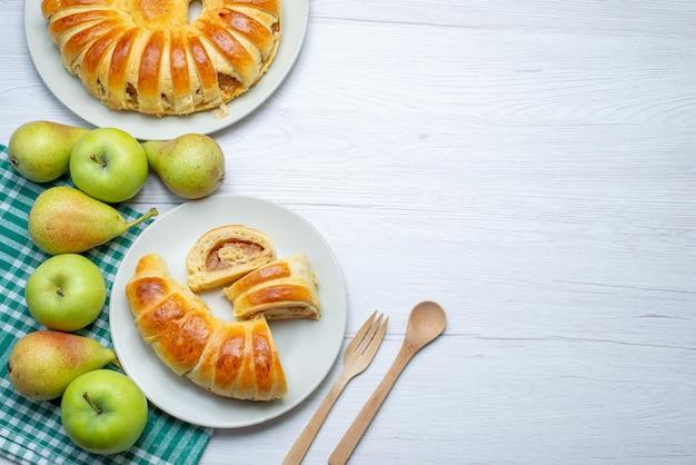 Top vue lointaine cuit délicieux bracelet de pâtisserie formé à l'intérieur de la plaque de verre avec des pommes et des poires sur un bureau blanc, pâtisserie biscuit sucré