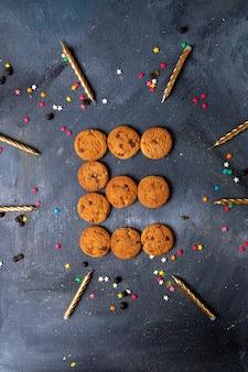 Top vue lointaine délicieux cookies au chocolat avec des bougies et des décorations sur le fond sombre biscuit biscuit thé sucré sucre