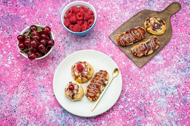 Top vue lointaine de délicieux gâteaux fruités à la crème et au chocolat à l'intérieur de la plaque blanche avec des fruits frais sur le fond rose gâteau biscuit sweet bake