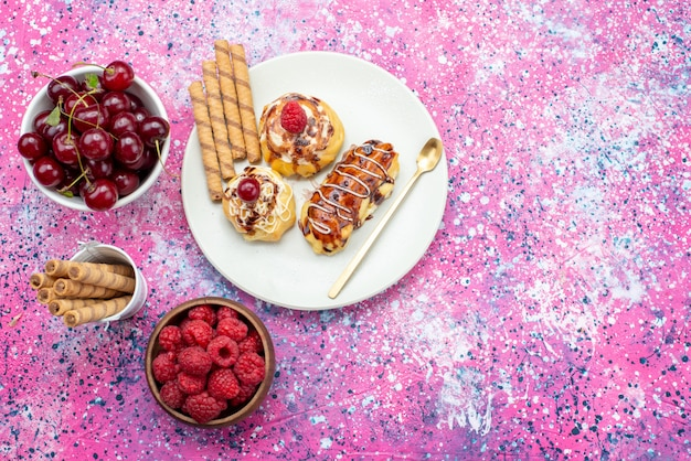 Top vue lointaine de délicieux gâteaux fruités à la crème et au chocolat à l'intérieur de la plaque blanche avec des fruits frais sur le gâteau fond rose sweet bake