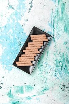 Top vue lointaine doux longs cookies à l'intérieur du moule à gâteau noir sur la surface bleue