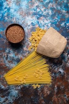 Top vue lointaine pâtes crues jaunes formées depuis longtemps et peu partout sur l'arrière-plan coloré pâtes italie repas alimentaire