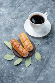 Top vue lointaine tasse de café avec de délicieux bracelets doux sur gris