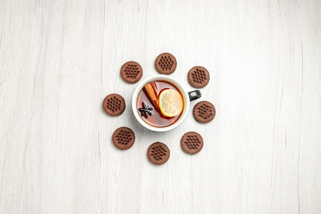 Top vue lointaine thé citron cannelle arrondi avec des biscuits sur la table en bois blanc