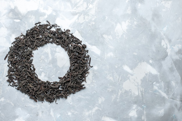 Top vue lointaine thé séché de couleur noire formant cercle sur la table lumineuse, couleur sèche de thé de grain