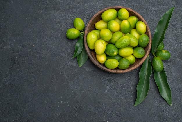 Top vue rapprochée d'agrumes bol d'agrumes avec des feuilles