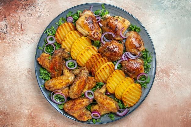 Top vue rapprochée ailes de poulet ailes de poulet tranches de pommes de terre frites herbes oignon sur la table