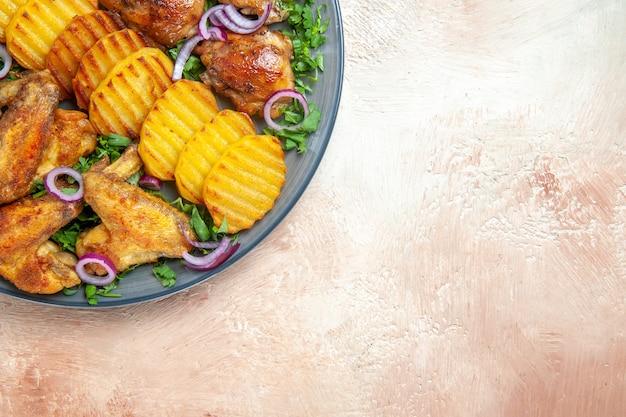 Top vue rapprochée ailes de poulet les pommes de terre frites appétissantes herbes de poulet et oignons
