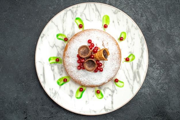 Top vue rapprochée d'une assiette à gâteau d'un gâteau appétissant avec des baies gaufres au sucre en poudre