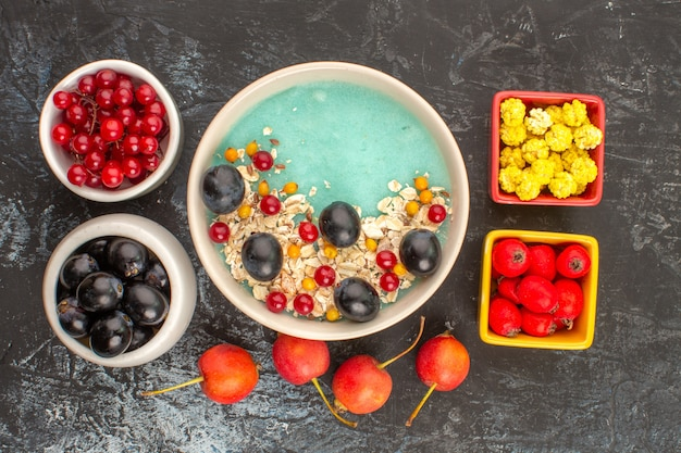 Top vue rapprochée de baies plaque de baies d'avoine bols de bonbons groseilles raisins noirs