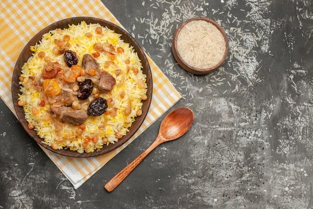 Top vue rapprochée bol de riz pilaf cuillère un appétissant pilaf sur la nappe à carreaux