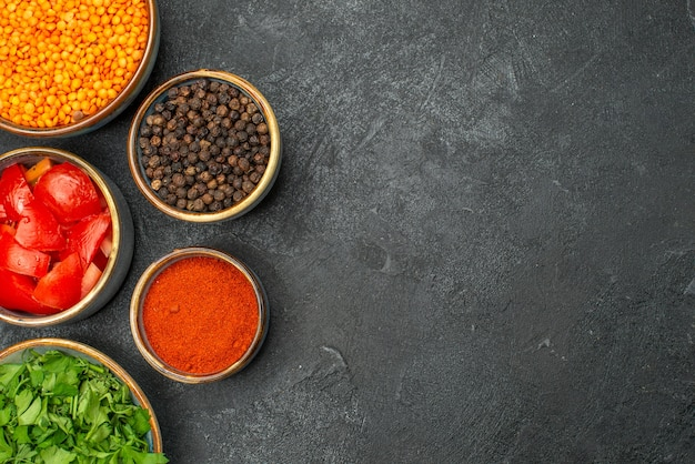 Top vue rapprochée bols de lentilles d'herbes de lentilles tomates épices poivre noir