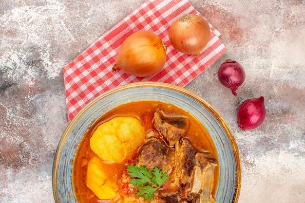 Top vue rapprochée bozbash soupe serviette de cuisine oignons jaunes et rouges sur fond nude